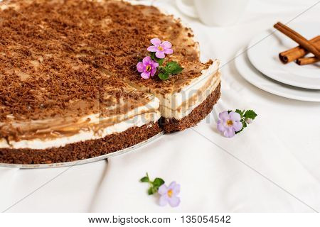 Traditional caramel cheesecake with chocolate and flower on white plate