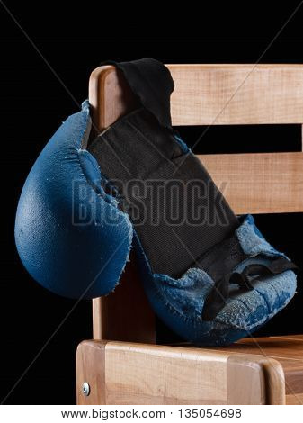 Old boxing or karate gloves hang on the bench black background. Retirement concept