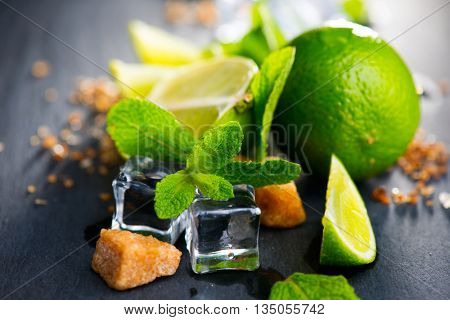 Mojito cocktail ingredients on a table in summer bar, Alcohol cocktails with Rum, lime, mint, ice cubes and brown sugar closeup, Party drink. Isolated on black background