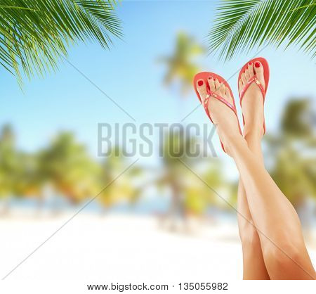 Sexy smooth woman legs with tropical beach on background. Cosmetics concept for summer