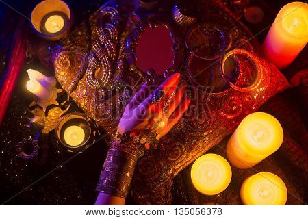 Golden Shiny Oriental Jewelry and Accessories: Female Hands with beautiful National Indian Jewellery Eastern Fairy Tale (Harem) Wedding Fashion and Beauty. Eastern Treasure Chest by Candlelight. Luxury Arabian Interior details.
