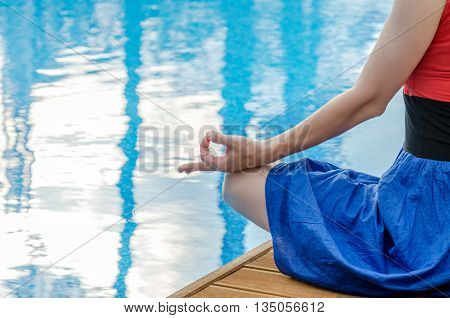 Young woman meditating on a wooden deck in lotus position