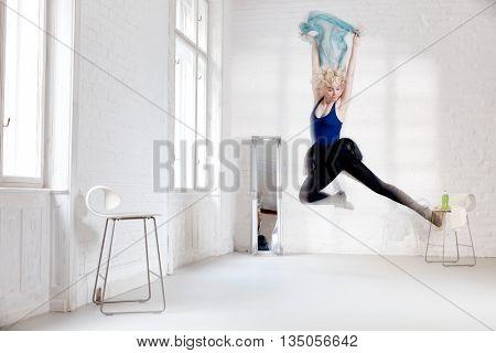 Female dancer practicing in studio, jumping, flying, enjoying dancing.