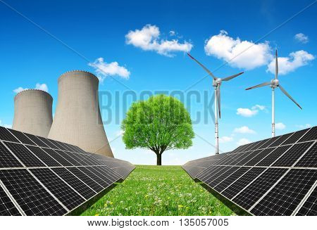 Solar panels before a nuclear power plant and wind turbines. Energy resources concept.
