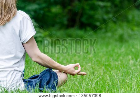 Woman doing yoga in the park in the morning