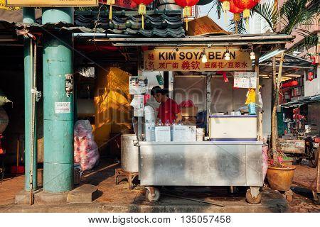 KUALA LUMPUR MALAYSIA - MARCH 17: Boy working at popular soya stall at Petaling Street in Chinatown Kuala Lumpur Malaysia on March 17 2016.