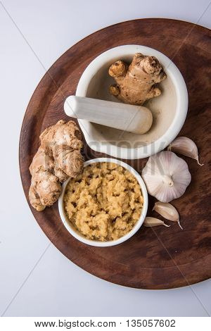 ginger and garlic paste or puree with 1 ginger and 1 garlic, closeup, selective focus, isolated on white background