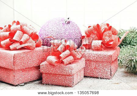 Christmas purple ball with red gift boxes on a light background. Christmas background