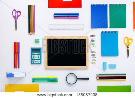 Blank small chalkboard with group of school supplies on a white background. Flat lay top view