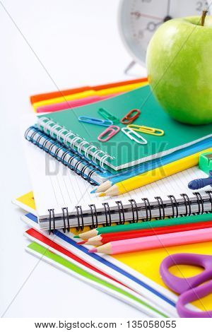 Closeup school supplies with green apple and alarm clock on a white background. Back to school concept