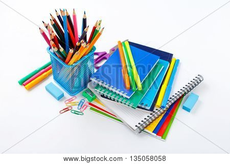 Back to school concept. Notebook and copybook stack with metal holder pencils pens paper clips sharpener and eraser on a white background
