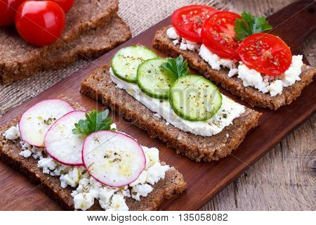 Closeup of black bread with feta cheese tomato, cucumber and radish on cutting board, selective focus