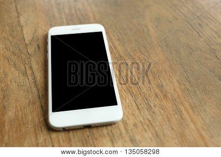 white color smartphone on a wooden desk