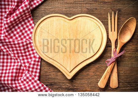 Heart shaped cutting board with a red checkered tablecloth on wooden table