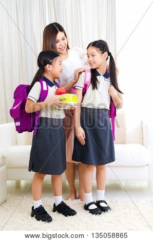 Asian mother get her daughters ready to school