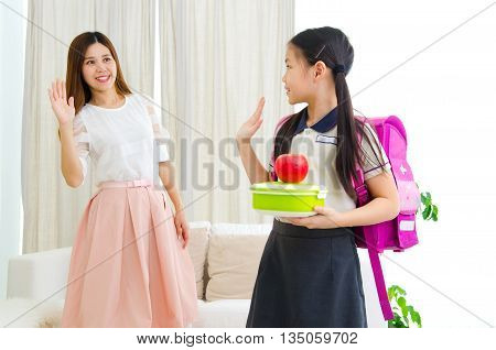 Asian child going to school and saying goodbye to her mother