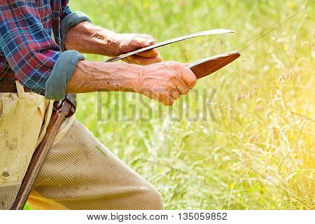 Farmer with beard sharpening his scythe for using to mow the grass traditionally