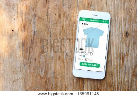 Smartphone with ecommerce screen website on wooden background