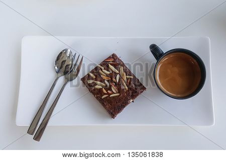 Chocolate brownies on plate and coffee mug, on white table