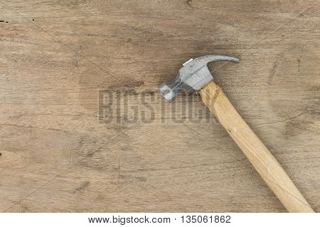 Small Hammer on wood background panel wooden