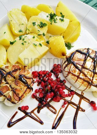 Camembert cheese with roasted potatoes currants and garlic. Food theme. International cuisine. Decorated plate. One portion. Lunch menu.