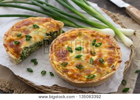 Mini quiche with green onions and cheese on a wooden background