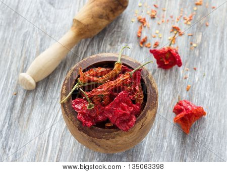 Various dried red chilli pepper in a mortar for grinding with a pestle on a wooden table