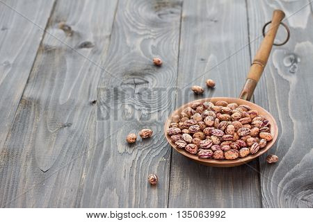 Dry borlotti beans in a copper bowl on a wooden table, selective focus