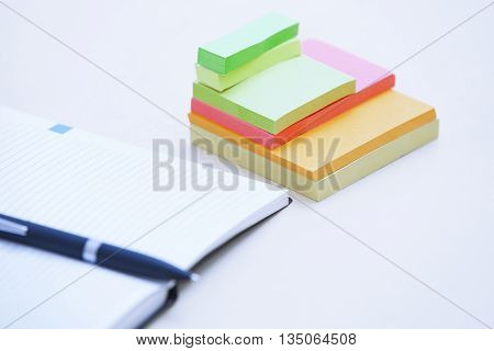 Ballpoint pen on the notepad and adhesive notes on a table
