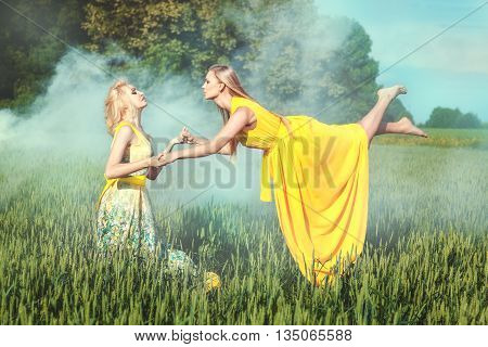 Two women hold each other's hands. One woman levitates over the field.