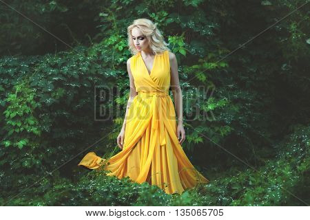 Delightful woman dressed in a yellow dress she is among the bushes in the forest.