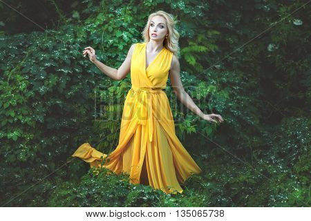 Charming woman with a surprised face she is dressed in a yellow dress and be in the woods.