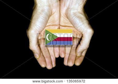 Flag of Comoros in hands isolated on black background.
