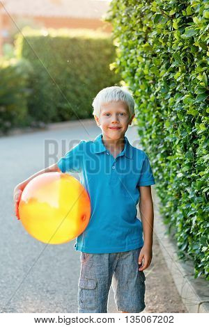 Portrait of a positive boy (6 years) with a ball on a summer day ,outdoor. Childhood.