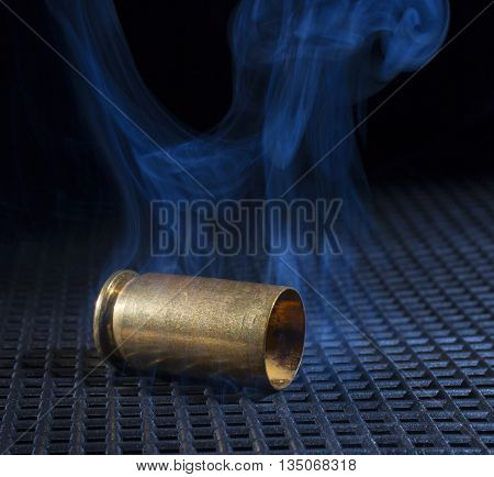 Empty shell from a semi automatic handgun that is smoking