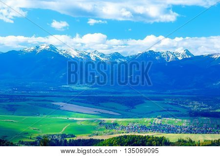 Beautiful landscape green and yellow meadow with field and snow mountain and village. Slovakia Central Europe Liptov. Mountain High Tatry