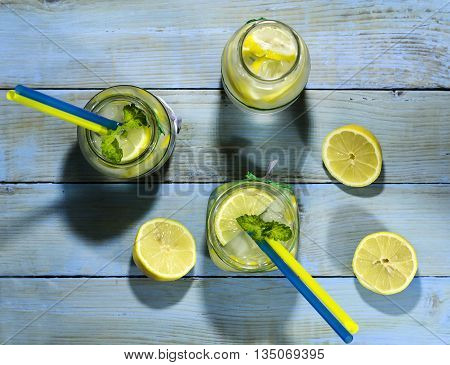 Cold lemonade in bottles with lemons on a blue wooden background. Top view