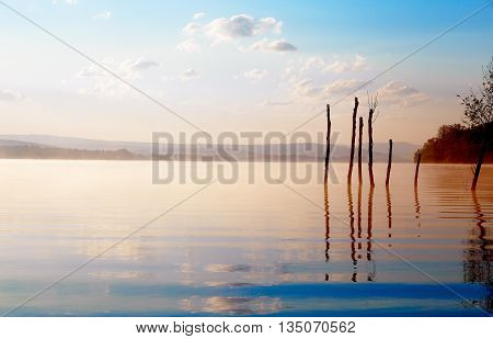 beautiful lake with mountains in the background at sunrise. Trees in water and morning fog