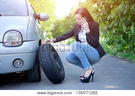 Sad woman calling assistance service after unexpected vehicle breakdown