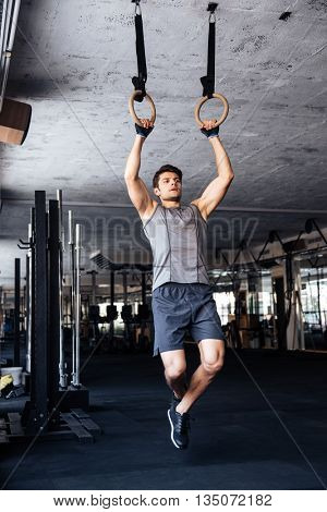 Fitness handsome young man doing dipping exercise using rings in the gym