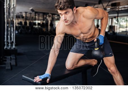 Handsome fitness man lifting kettle ball at the gym
