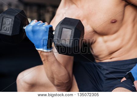 Closeup portrait of a young bodybuilder workout with dumbbell in fitness gym