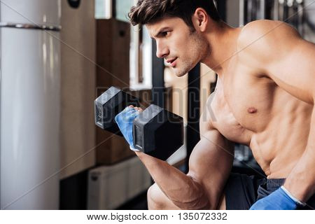 Portrait of a male muscular bodybuilder workout with dumbbell in fitness gym