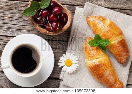 Croissants, coffee cup and cherries on wooden table. Top view. Breakfast concept