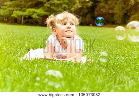 girl making soap bubbles outdoors in the summer