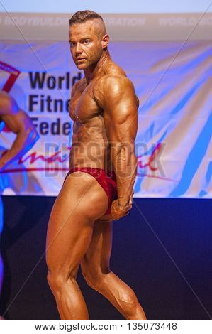MAASTRICHT THE NETHERLANDS - OCTOBER 25 2015: Male bodybuilder flexes his muscles and shows his best triceps pose at the World Grandprix Bodybuilding and Fitness of the WBBF-WFF
