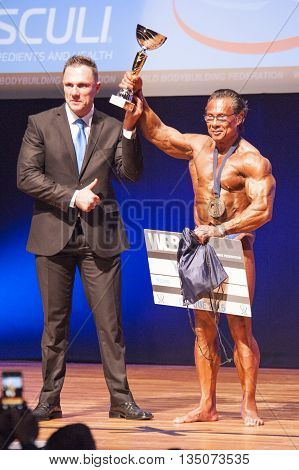 MAASTRICHT THE NETHERLANDS - OCTOBER 25 2015: Male bodybuilder celebrates his victory on stage with official at the World Grandprix Bodybuilding and Fitness of the WBBF-WFF