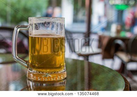 glass of light beer in restaurant, blur background