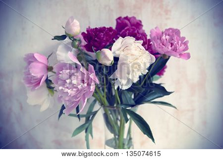 Bouquet of beautiful peonies on vintage background