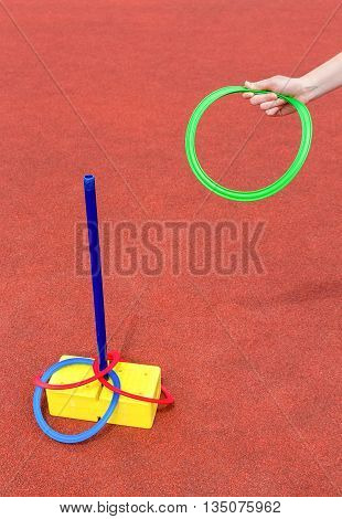 Arm throwing colored rings around tube on gravel